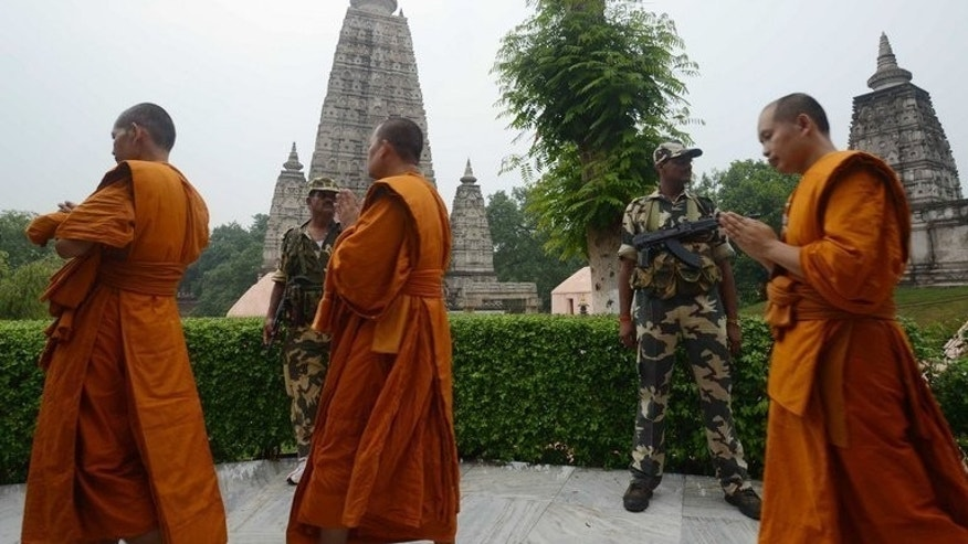 Indian soldiers stand guard as Buddhist monks walk past in prayer at the Mahabodhi temple complex in Bodh Gaya, on July 8, 2013. Attackers who staged serial blasts at one of Buddhism's holiest sites this week also placed a bomb on a giant stone-carved idol of the Buddha that did not explode, police told AFP.