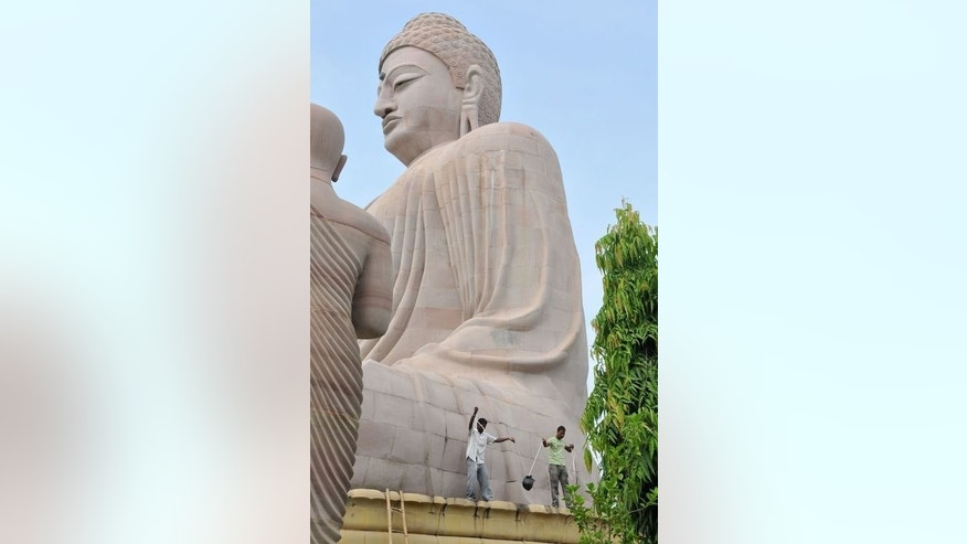 Indian bomb disposal personnel recover an unexploded bomb from the great statue of Buddha at the Mahabodhi temple complex in Bodh Gaya, on July 7, 2013. Attackers who staged serial blasts at one of Buddhism's holiest sites this week also placed a bomb on a giant stone-carved idol of the Buddha that did not explode, police told AFP.