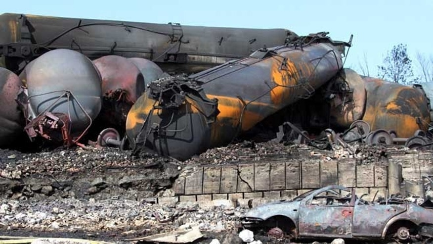 July 8, 2013: This photo provided by Surete du Quebec, shows wrecked oil tankers and debris  from a runaway train in Lac-Megantic, Quebec, Canada.  A runaway train derailed igniting tanker cars carrying crude oil early Saturday, July 6.  At least thirteen people were confirmed dead and nearly 40 others were still missing in a catastrophe that raised questions about the safety of transporting oil by rail instead of pipeline.