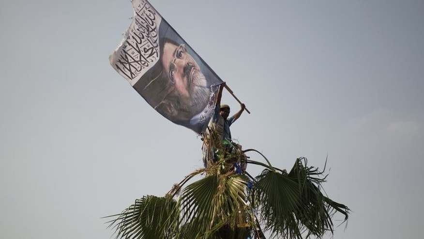 A man waves a giant flag with the portrait of ousted president Mohamed Morsi as thousands of his supporters gather in front of the Rabaa al-Adawiya mosque on July 9, 2013 in Cairo. Egypt's main coalition, which backed the military ouster of Morsi, denounced a roadmap granting the interim president extensive powers ahead of new elections, further complicating a bloody transition to civilian rule.