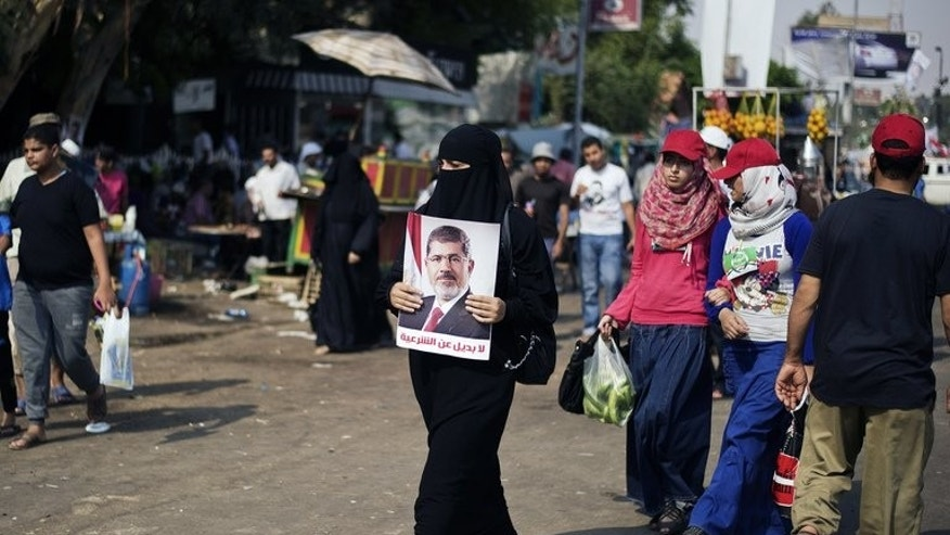 A woman holds a portrait of ousted president Mohammed Morsi as thousands of his supporters gather in front of Cairo's Rabaa al-Adawiya mosque on July 9, 2013. Egypt's main coalition, which backed the military ouster of Morsi, denounced a roadmap granting the interim president extensive powers ahead of new elections, further complicating a bloody transition to civilian rule.