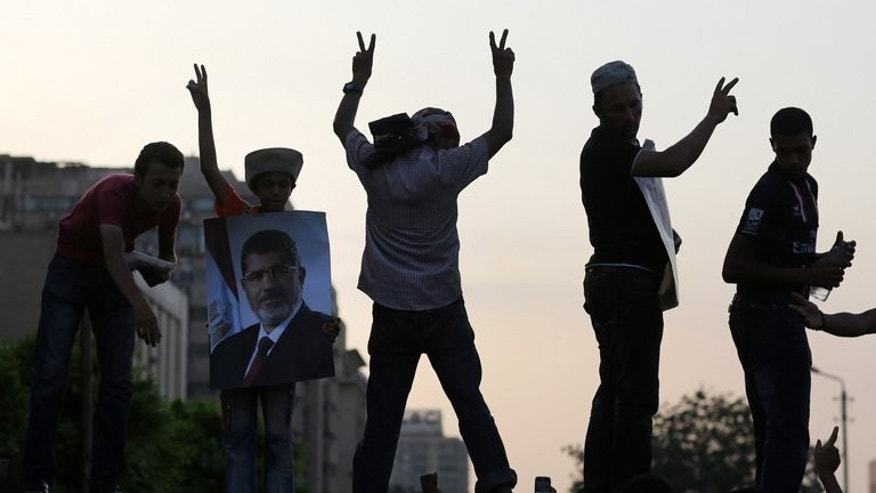 Supporters of deposed president Mohamed Morsi (on the poster) flash the victory sign during a rally outside the headquarters of the Republican Guard in Cairo on July 9, 2013. Egypt's main coalition, which backed the military ouster of Morsi, denounced a roadmap granting the interim president extensive powers ahead of new elections, further complicating a bloody transition to civilian rule.