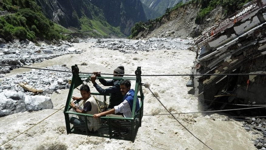 Indian villagers cross the Alaknanda river on June 30, 2013, following flash floods in Uttarkhand state. Indian authorities have raised to 5,500 the estimated number of people who perished in devastating floods that swept Uttarakhand.