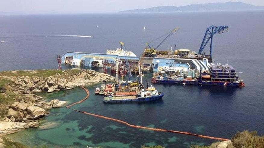 July 8, 2013: The Costa Concordia cruise ship lies on its side in the waters of the Tuscan island of Giglio, Italy. The luxury cruise ship ran aground off the coast of Tuscany on Jan 13, 2012, sending water pouring in through a 160-foot (50-meter) gash in the hull and forcing the evacuation of some 4,200 people from the listing vessel early.