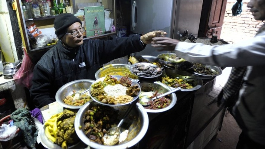 "A Nepalese Newari bhatti vendor prepares food for customers at his shop in Kathmandu on January 9, 2012. It might not look appetising to Westerners but dozens of indigenous Newars gather daily in his ""bhatti"" as part of a centuries-old social scene largely missed by the thousands of tourists who come to Nepal in search of culture."