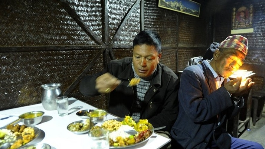 "Customers eat at an ethnic Newari cuisine shop in Kathmandu on January 9, 2012. Hidden in the capital's myriad labyrinthine alleyways are hundreds of these traditional hole-in-the-wall eateries -- ""speakeasies"" to the locals -- serving potent home brew and various buffalo meat snacks."