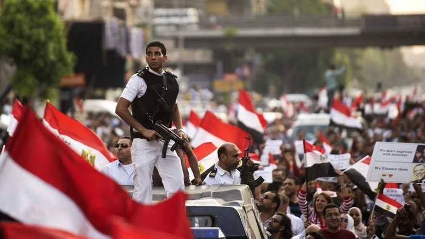An armed Egyptian policeman scouts buildings among protesters demonstrating against deposed president Mohammed Morsi on July 7, 2013 in Cairo. Egypt's National Salvation Front, the main coalition that backed Morsi's overthrow, denounced on Tuesday a decree which invests the new interim president with extensive powers and sets a new election schedule.