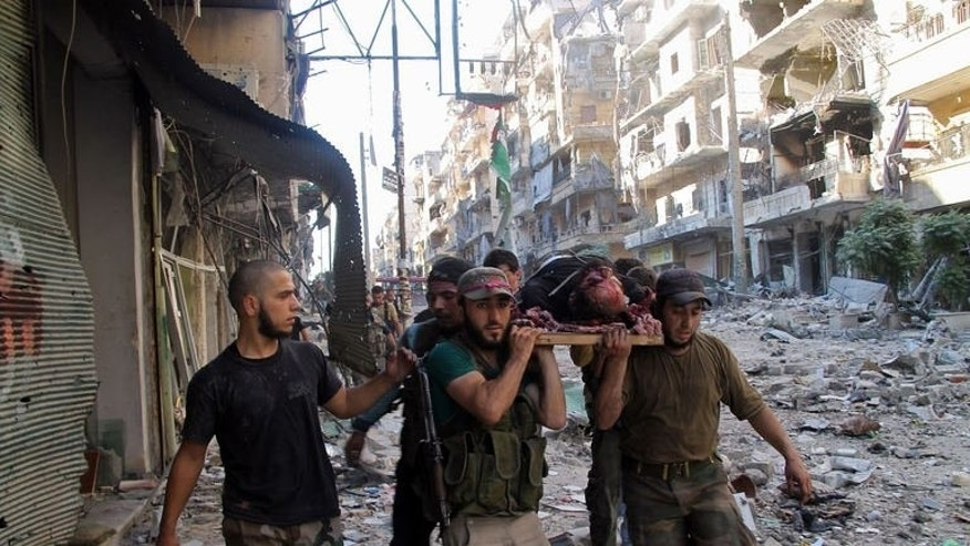 Opposition fighters carry an injured comrade during a battle against government forces in the Salaheddine neighbourhood of Aleppo on July 8, 2013. Syria's ruling Baath party has replaced its top leadership in a surprise move, while UN head Ban Ki-Moon called on all parties in the war to observe a truce during the Muslim holy month of Ramadan.