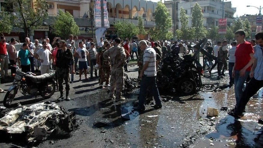 A Syrian Arab News Agency image shows Syrians gathering at the scene of a car bomb attack in Homs on July 8, 2013. Troops loyal to President Bashar al-Assad have advanced into the rebel-held Khaldiyeh district of Homs on the 10th day of an assault there.
