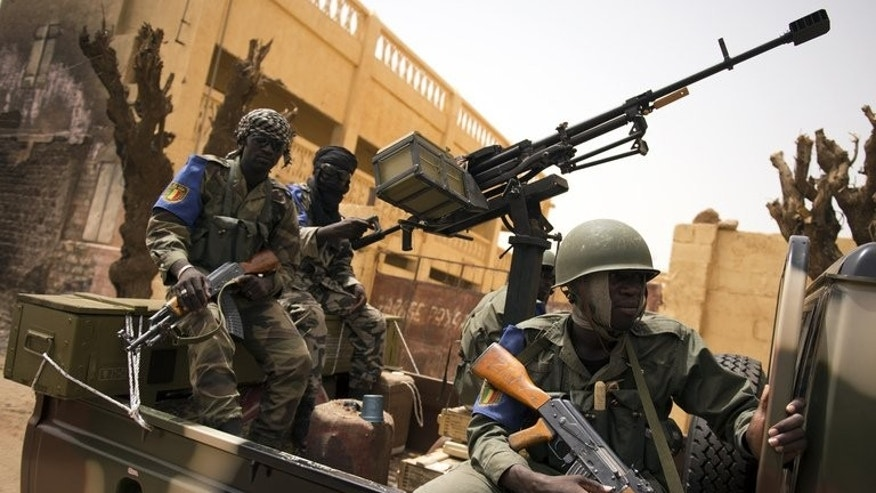 Malian soldiers patrol in the streets of Gao on June 13, 2013. Two Malian civilians are fighting for their lives after being shot in Kidal, a medical source said on Tuesday, with tension boiling over five days after troops entered the flashpoint northeastern town to secure it for nationwide elections.