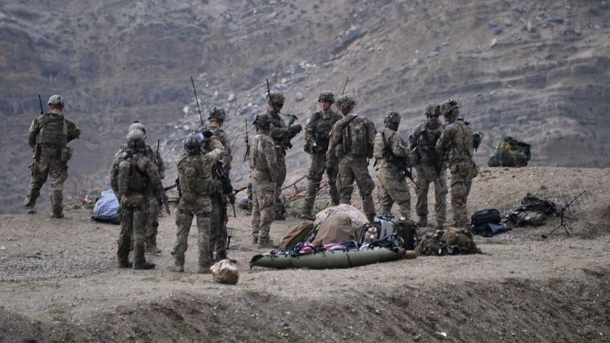 US soldiers gather near the scene of a helicopter crash in the Pachir Wa Agam district of Nangarhar province on April 9, 2013. Hoped-for peace talks between the Afghan government and Taliban insurgents will not bear fruit until 2015 at best, a year after US-led troops leave the country, the EU's Afghanistan envoy has warned.