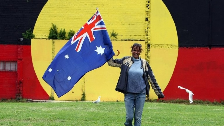 A woman carries the national flag in front of an Aboriginal flag in Sydney on February 13, 2008. Australian Prime Minister Kevin Rudd on Wednesday used the 50th anniversary of the indigenous land rights movement to pledge a referendum on recognising the country's Aborigines in the constitution if Labor is re-elected.