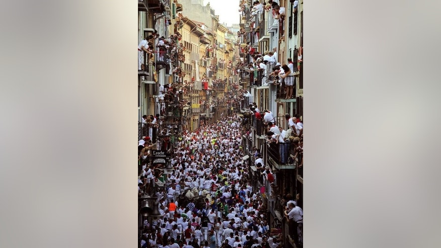 People watch participants running in front of bulls during the San Fermin Festival, in Pamplona, northern Spain, on July 10, 2013. Three people were injured as huge fighting bulls knocked over daredevils on a breakneck bull run through the cobbled streets of Pamplona.
