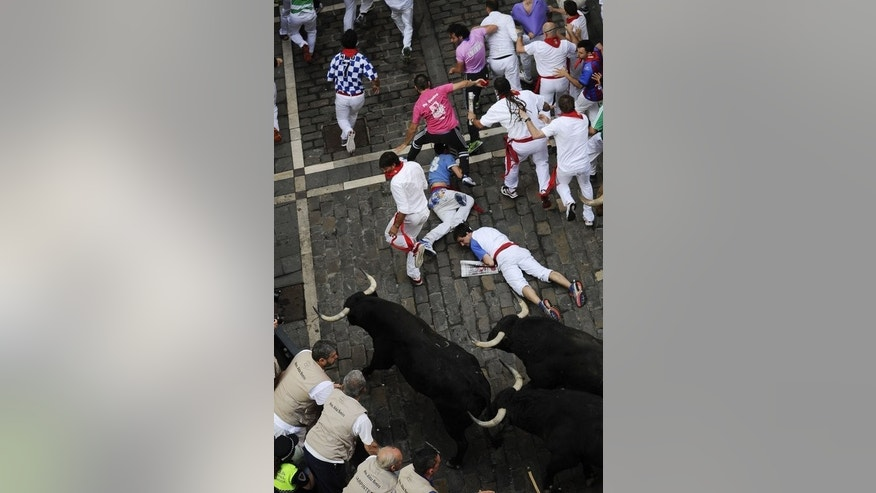 Participants run and fall in front of bulls during the fourth bull run of the San Fermin Festival in Pamplona, northern Spain, on July 10, 2013. Three people were injured as huge fighting bulls knocked over daredevils on a breakneck bull run through the cobbled streets of Pamplona.
