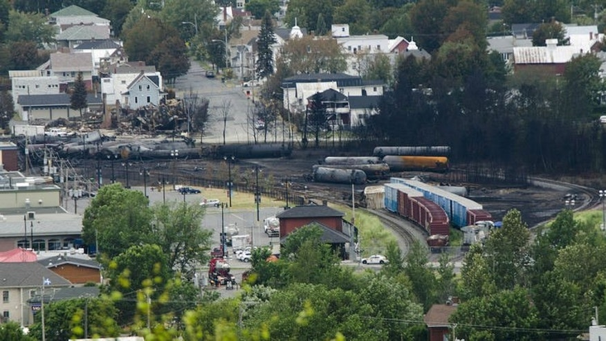 Scorched oil tankers are seen July 10, 2013 at the train derailment site in Lac-Megantic, Quebec. Twenty people have been confirmed dead and 30 remain unaccounted for with little hope of being found alive following the explosive train crash, Quebec provincial police inspector Michel Forget told reporters