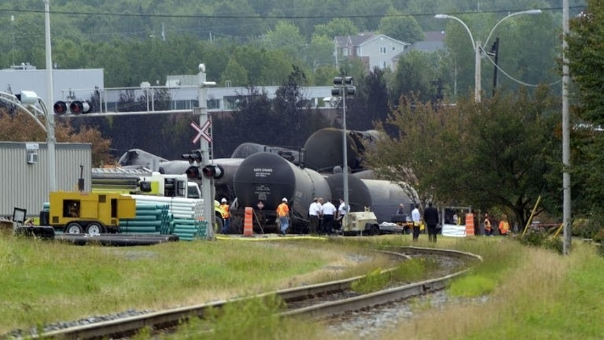 "Investigators work at the train derailment site July 9, 2013 in Lac-megantic, Quebec, Canada. The disaster that ""probably"" killed as many as 50 people was likely the result of an engineer's failure to set the brakes on an unmanned train owned by a US railway company, officials said."
