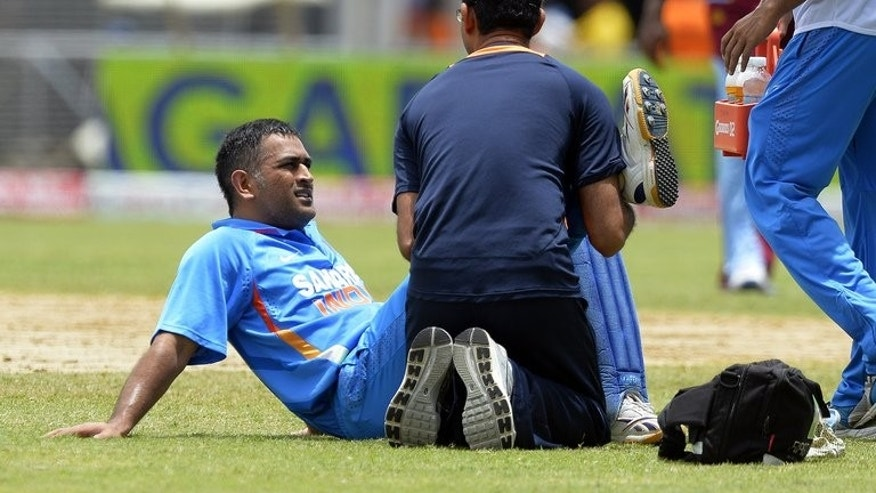 Mahendra Singh Dhoni is treated after injuring his right leg against West Indies in Kingston on June 30. India and Sri Lanka meet yet again, this time in the final of the Tri-Nation Series at Queen's Park Oval on Thursday, amid increasing speculation that Dhoni will be back to the lead the World Cup and Champions Trophy holders.