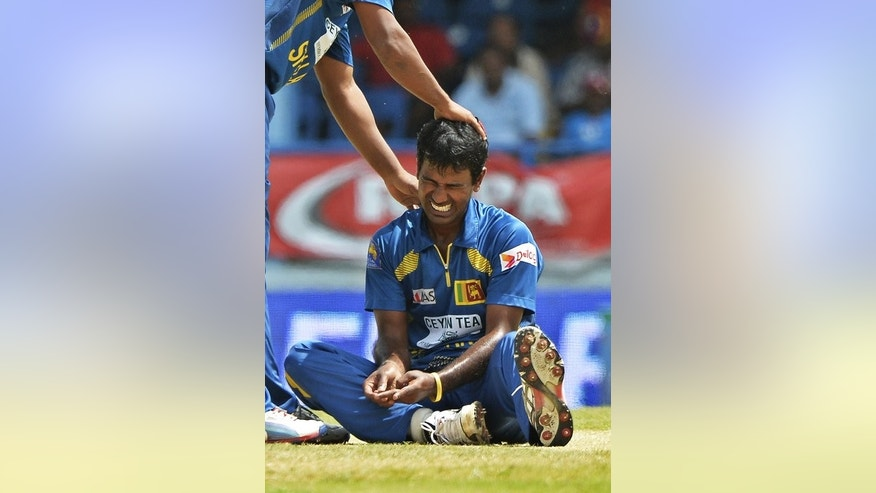 Nuwan Kulasekara grimaces in pain after hurting a finger in Port of Spain on Monday. Sri Lanka have their own injury concerns with a question mark lingering over the availability of fast-medium bowler Kulasekara, who injured a finger while attempting to take a return catch off Chris Gayle against the West Indies.