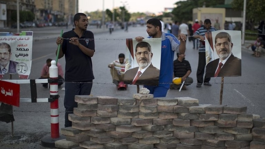 "Men hang portraits of Mohamed Morsi on a barricade in Cairo on July 7. Egypt's ousted president is in a ""safe place"" following his overthrow by the military, a foreign ministry spokesman told reporters on Wednesday, adding that no charges had been levelled against him yet."