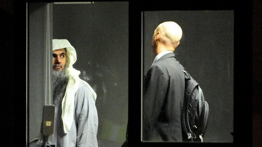 A photo release by the Home Office shows Abu Qatada waiting with an escort to board a jet at RAF Northolt, west London, on July 7, 2013. A military court has postponed until next week a bail application by the Islamist cleric, who faces terror charges in Jordan following his deportation from Britain.