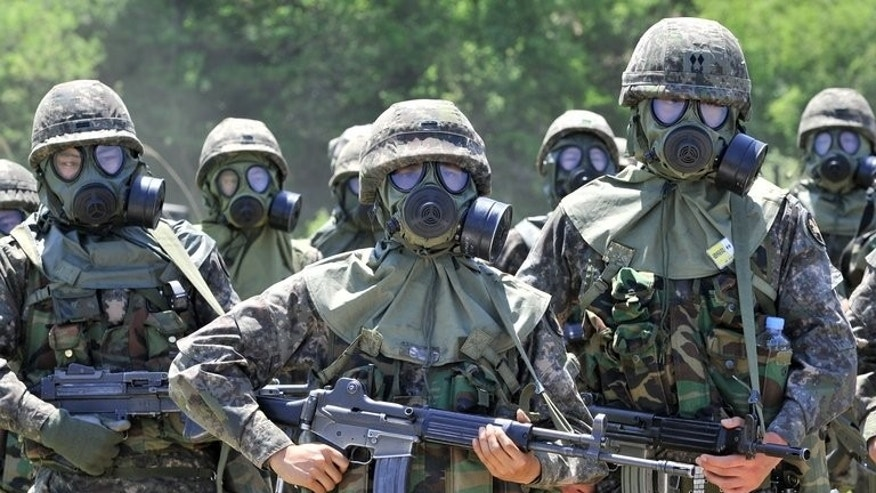South Korean soldiers wearing gas masks take part in a training exercise in in Yeoncheon, May 16, 2013. Military service is taken extremely seriously South Korea, which remains technically at war with North Korea because their 1950-53 conflict ended with a ceasefire rather than a peace treaty.