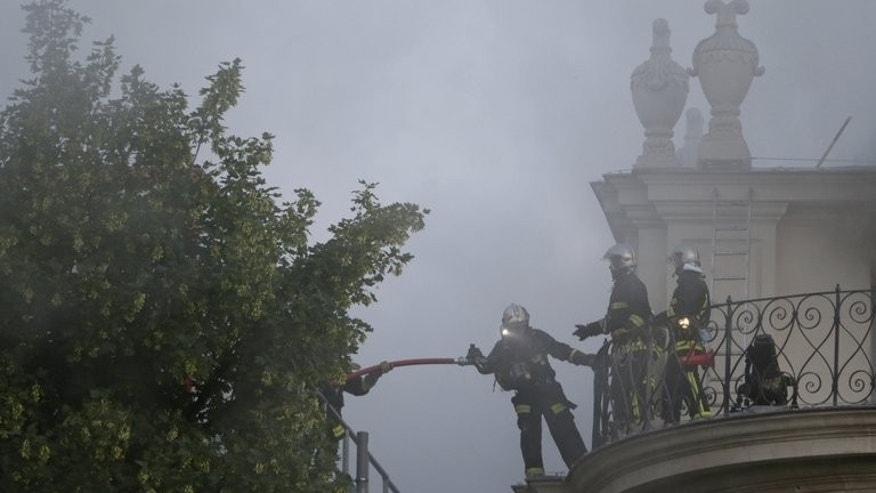 Firemen fight a blaze at the 17th-century Lambert Hotel in Paris on July 10, 2013. Dozens of firefighters battled a major blaze at the central Paris landmark, a private mansion that was bought by a Qatari prince in 2007.