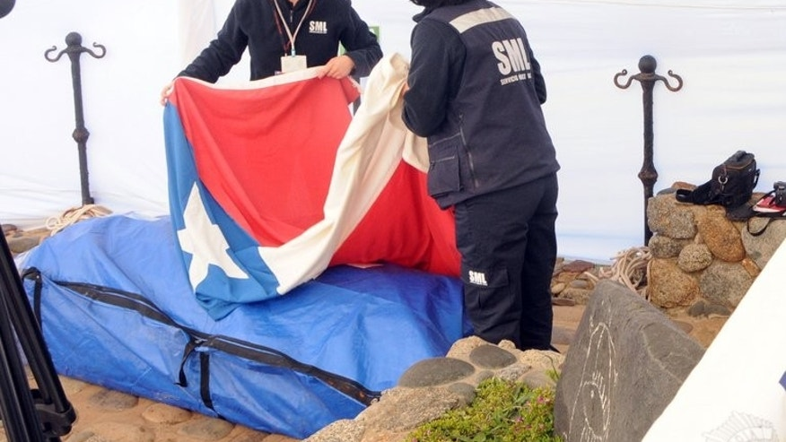 Coroner's office's personnel cover the coffin with the remains of Chilean poet Pablo Neruda with the Chilean flag, in Isla Negra, some 120 km (75 miles) west of Santiago, on April 8, 2013. A judge ordered the remains of Neruda to be tested in Spain to determine whether he died of poisoning, court records showed Wednesday.