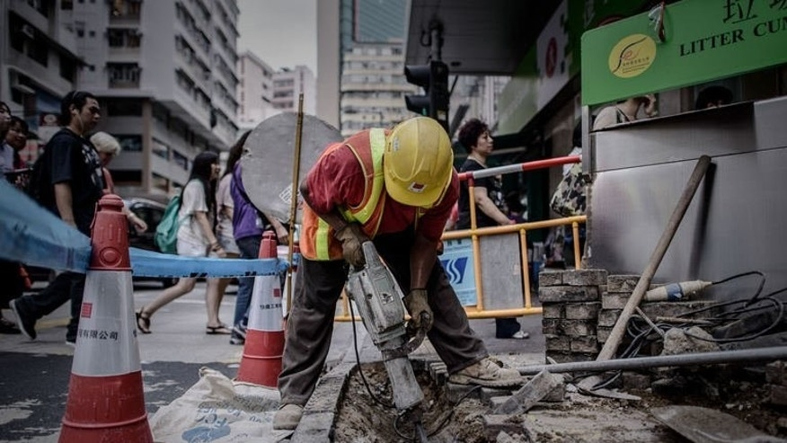 A worker uses a pneumatic drill on the pavement as pedestrians walk past in Hong Kong on July 9, 2013. With its pounding construction sites and constant roar of traffic, Hong Kong is a cacophony of noise with residents calling on authorities to keep a lid on the din for the sake of public health.