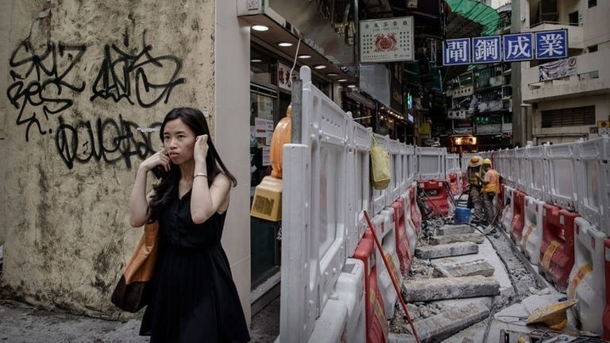 A woman blocks her ears as she walks past roadworks in Hong Kong on July 9, 2013. Rapid growth in the past 30 years means residents live cheek by jowl even on the outskirts of the city beside busy main roads.