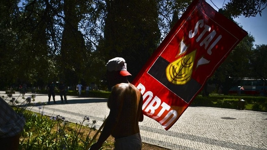 A man carries a flag as he protests with hundreds of workers gathered near the Belem Palace during a general public workers demonstration demanding the resignation of the government and calling for snap elections in Lisbon, on July 6, 2013.