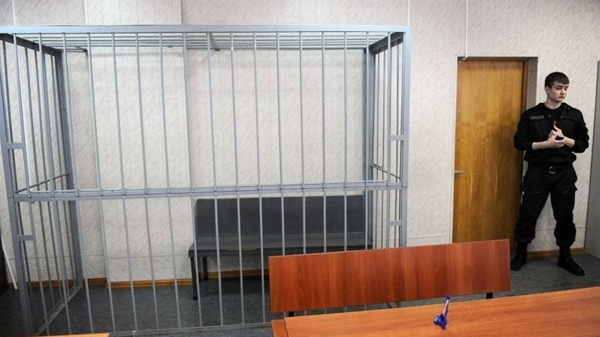 A security guard stands next to an empty defendant's cage in a Moscow court on March 27, 2013, during a hearing in the posthumous trial of lawyer Sergei Magnitsky. A court is expected on Thursday to find him guilty,even though he died in 2009.