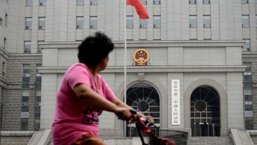 A woman rides a bicycle in front of a Beijing courthouse on July 8, 2013. China's Communist authorities are touting a suspended death sentence for an ex-minister as proof new leaders are serious about their avowed corruption crackdown, but scepticism remains in the absence of systematic reforms.