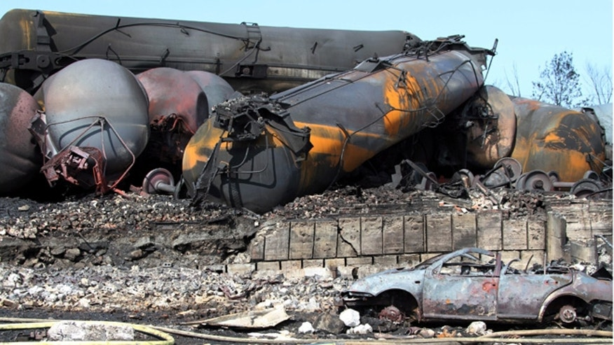 July 8, 2013: This photo provided by Surete du Quebec, shows wrecked oil tankers and debris from a runaway train in Lac-Megantic, Quebec, Canada.  A runaway train derailed igniting tanker cars carrying crude oil early Saturday, July 6.