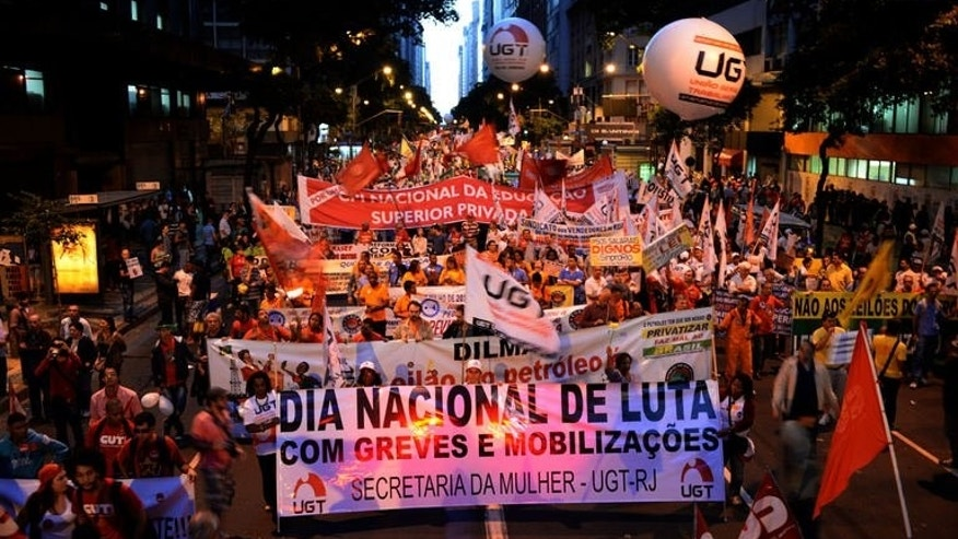 Brazilian workers march in Rio de Janeiro on July 11, 2013. Striking workers blocked key highways and staged peaceful marches across Brazil Thursday in a day of industrial action called by major unions to demand better work conditions and tougher government measures to contain rising inflation.