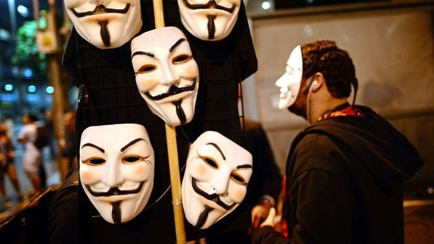 Guy Fawkes masks are sold in the streets of Rio de Janeiro as Brazilian workers march on July 11, 2013.