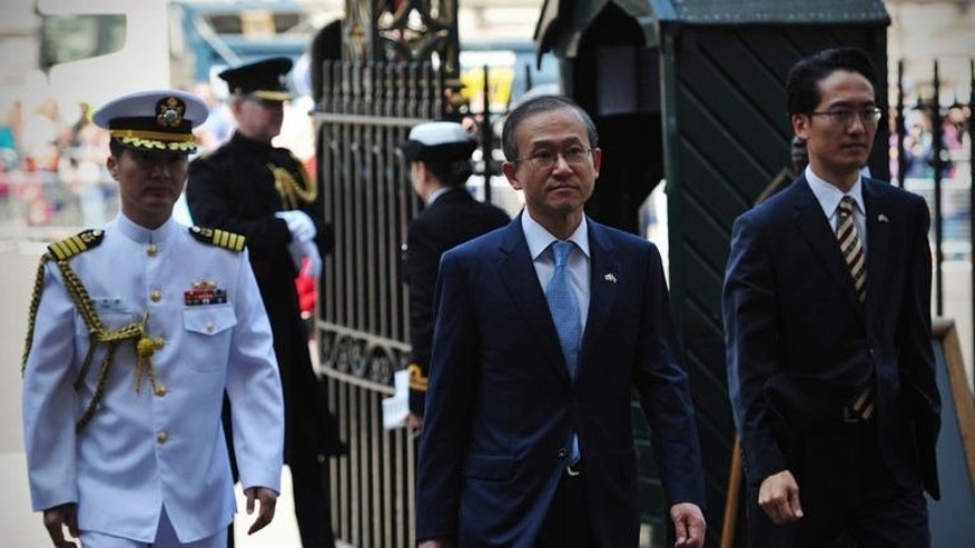 South Korean ambassador Sungnam Lim (centre) arrives for a memorial service at Westminster Abbey in central London, on July 11, 2013. Nearly 300 elderly veterans have marched through London as Britain marked the 60th anniversary of the Korean War armistice.
