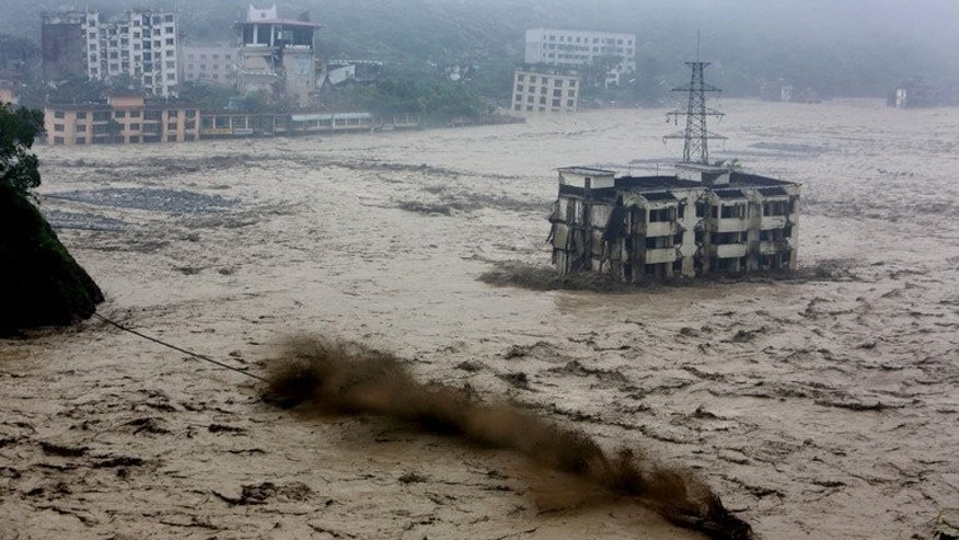 Flood waters sweep through Beichuan in southwest China's Sichuan province July 9, 2013. Heavy rain in southwest China has left at least nine dead and 62 missing, officials reported Thursday, after landslides crushed homes, bridges collapsed, and dozens of villages were cut off.