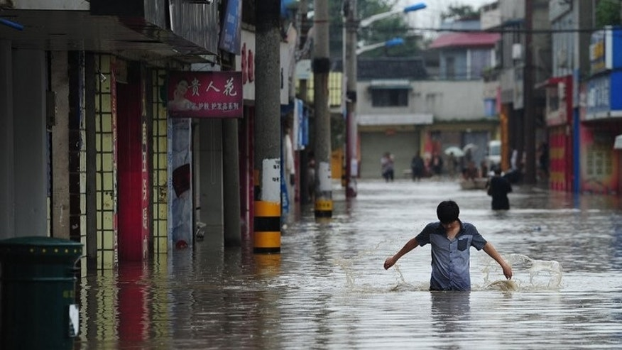 Residents walk along a flooded street in a district in Chengdu, southwest China's Sichuan province July 9, 2013. Heavy rain in southwest China has left at least nine dead and 62 missing, officials reported Thursday, after landslides crushed homes, bridges collapsed, and dozens of villages were cut off.