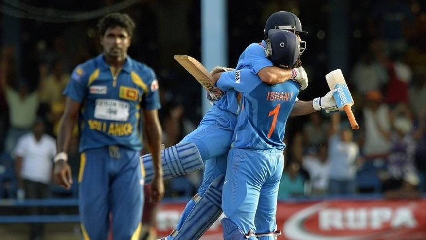 Indian captain Mahendra Singh Dhoni is lifted off the ground by teammate Ishant Sharma after hitting a boundary for six to seal victory over Sri Lanka on July 11, 2013. Dhoni dragged his side to a pulsating one-wicket victory in the final of the Tri-Nation Series at Queen's Park Oval.