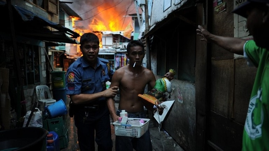 A Filipino policeman escorts a resident from his burning house as a fire engulfs a shanty town in Manila, on July 11, 2013. Three hundred homes were destroyed in a fire that tore through a slum in the Philippine capital, forcing residents to make dramatic escapes.