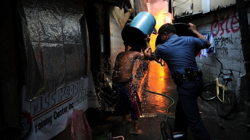 A policeman uses a bucket to protect himself from the heat as he helps a resident escape a fire that swept though a shanty town in Manila, on July 11, 2013. There were no immediate reports of casualties from the blaze, which occurred mid-morning amid government plans to relocate thousands of families living in areas vulnerable to floods and typhoons. AFP PHOTO / TED ALJIBE
