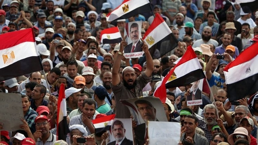 Supporters of deposed Egyptian president Mohamed Morsi hold portraits of him and national flags during a rally on July 9, 2013 outside Cairo's Rabaa al-Adawiya mosque. Egypt's new leadership was seeking to push forward with forming a new government on Thursday as police sought to arrest the leader of the Islamist movement defiantly backing Morsi.