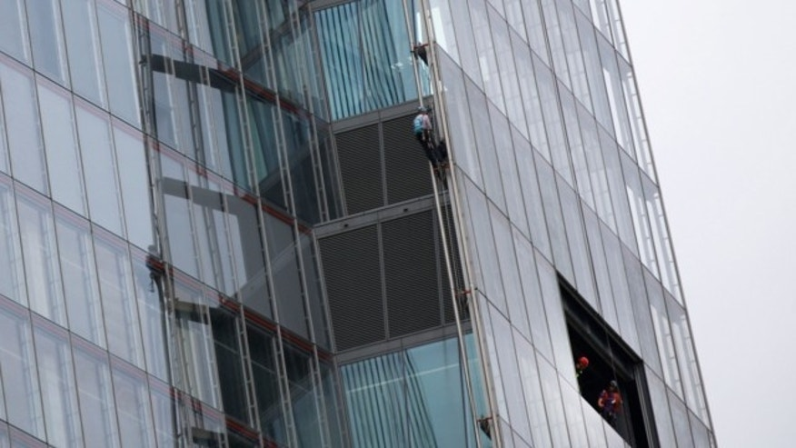 July 11, 2013: One of six Greenpeace protesters climbs up The Shard, the tallest building in western Europe, as workers look from a window, during a protest against the oil company Shell's drilling in the Arctic
