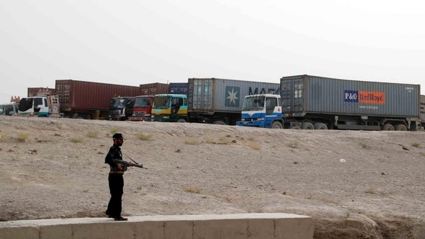 A Pakistani security serviceman stands guard beside container trucks parked at the border town of Chaman on July 27, 2012. A bomb explosion on Thursday killed at least two people and wounded eight others including four paramilitary Frontier Corps (FC) officials in a southwestern Pakistani town near the Afghan border, officials said.