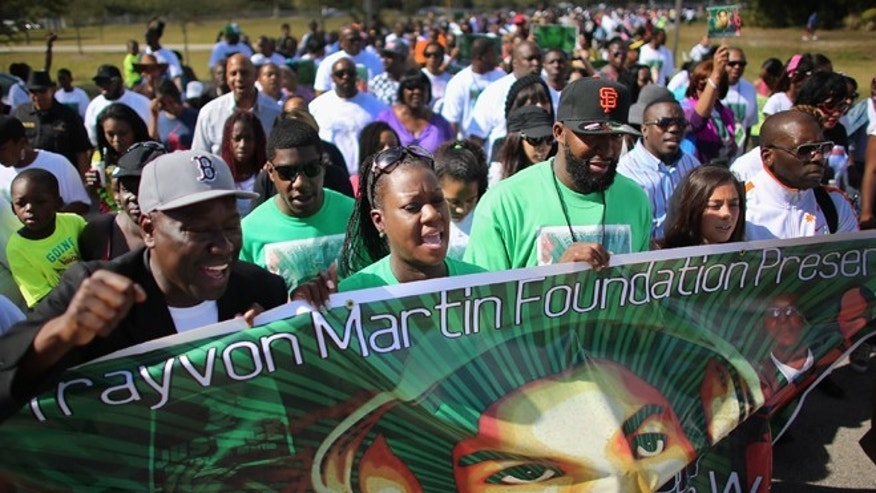 "Sybrina Fulton (2nd from L) and Tracy Martin (3rd from L) walk with supporters during the ""March for Peace"" at Ives Estate Park in honor of their late son, Trayvon Martin, on February 9, 2013 in Miami, Florida. (Photo by Joe Raedle/Getty Images)"