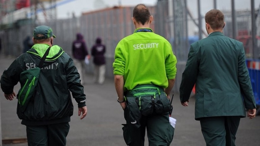 Security guards from the private firm G4S walk through the London 2012 Olympic Park in east London on July 18, 2012. The security giants G4S and Serco overcharged the government by tens of millions of pounds for the electronic tagging of criminals, including claiming they were tagging people who had died, the justice secretary said Thursday.