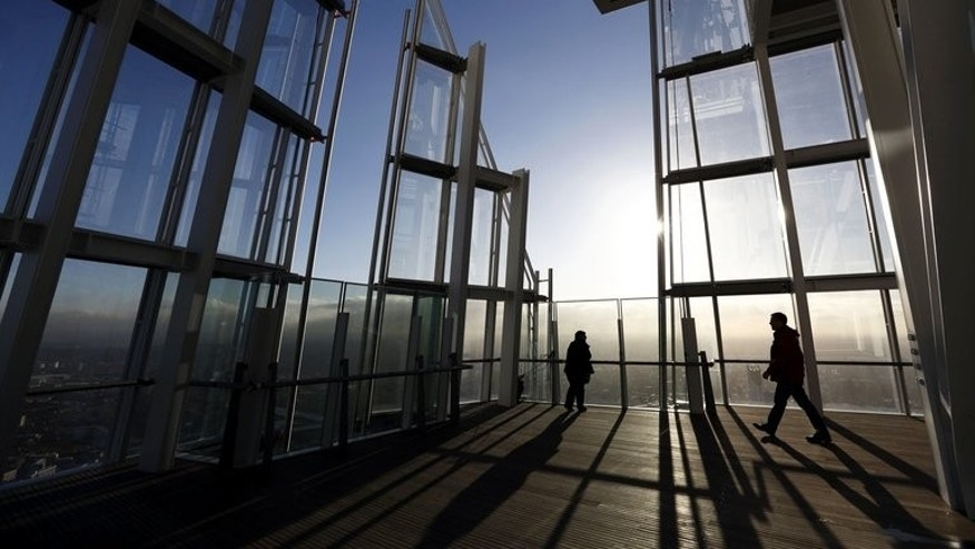 People admire the view of London from the 68th floor of the Shard in central London on January 9, 2013. Six women were attempting to climb London's 72-storey Shard skyscraper on Thursday morning in protest over Arctic oil drilling, the environmental group Greenpeace and police said.