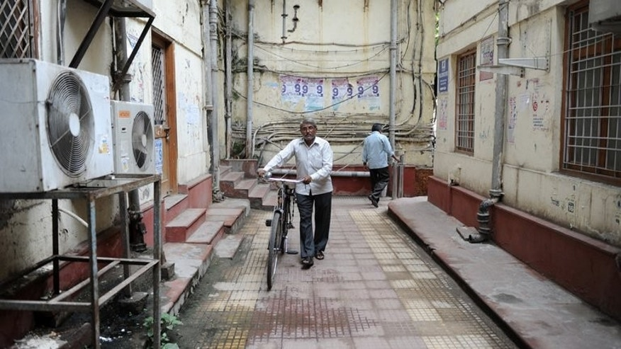 Telegram messenger Om Dutt wheels his bicycle at the Central Telegraph Office in New Delhi on July 10, 2013. In 2012, the number of telegrams dwindled to 40,000 and most of them were by Indian government departments conveying administrative messages to remote parts of the country.