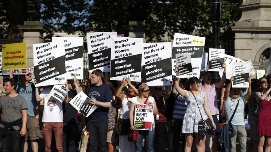 Abortion rights supporters hold placards in front of the gates of the Irish Parliament building in Dublin on July 10, 2013. Irish lawmakers on Friday voted in favour of controversial new legislation which will allow for abortion in limited cases where the mother's life is at risk, broadcaster RTE announced.