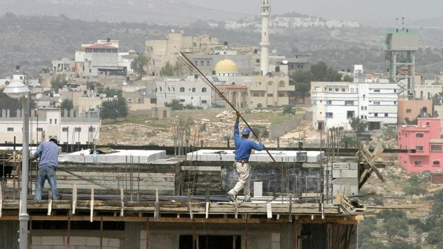 Palestinian men work at the construction site of a new neighborhood in the West Bank settlement of Elkana, on April 19, 2005.